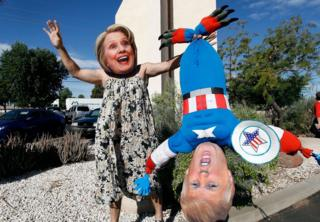 Hillary Clinton supporter Jorge Mendez of Glendale, Arizona wears a dress and Hillary Clinton mask