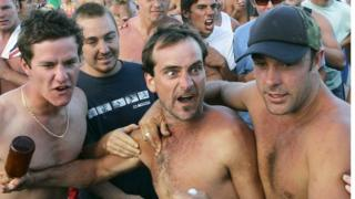 Men gesture during the violence on December 11, 2005