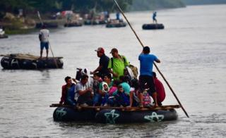 Several makeshift rafts carry migrants across the river