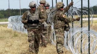 Militares en la frontera entre Estados Unidos y México colocan alambres de púas.