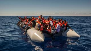 n this Tuesday July 19, 2016 photo, refugees and migrants from Eritrea, Mali, Bangladesh and other countries wait on board a dinghy to be rescued in the Mediterranean Sea, 27 kilometers (17 miles) north of Sabratha, Libya.