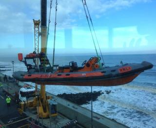 The lifeboat being lifted in the air