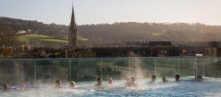 Bathers enjoying balmy weather as they bathe in Thermae Bath Spa