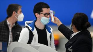 Os passageiros que usam máscaras ou coberturas devido à pandemia do Covid-19 têm a temperatura medida na fila do check-in da British Airways no aeroporto de Heathrow.