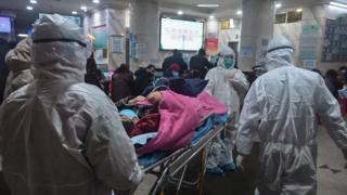 Medical staff carry a patient into a Wuhan Red Cross hospital