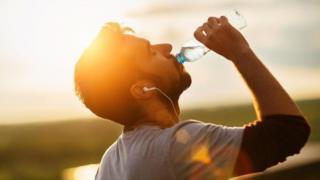 Hombre tomando agua de una botella