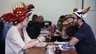 Friends sit down to drink a food during the traditional hat day during the CAMRA Great British Beer Festival at Olympia in London.