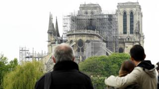 People hug while looking at Notre-Dame on 16 April 2019
