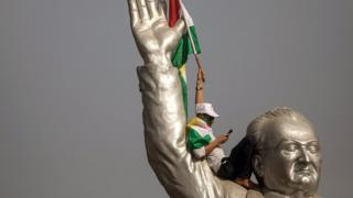 A supporter of Kurdish independence waves a flag while sat on the shoulder of a large stadium statue in Erbil.