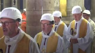 كهنة بخوذ بيضاء واقية في كاتدرائية نوتردام