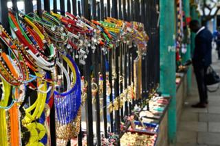 Necklaces featuring colourful beads and metal discs, as well as bracelet and other souvenirs are displayed on municipal railings.