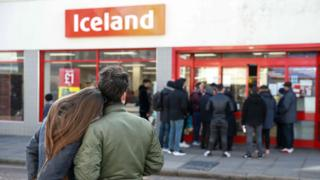 Shoppers look at a queue outside Iceland