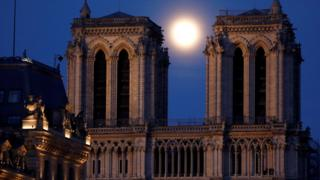 The pink supermoon rises between the two towers of Notre Dame Cathedral