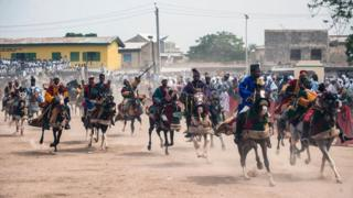 """Members of the Durbar procession race the final stretch to the Emir""""s palace in Kano, northern Nigeria on July 6, 2016"""