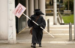 """A man in a 17th Century plague doctor""""s costume carries a sign in central Leeds on March 21, 2020, a day after the British government said it would help cover the wages of people hit by the coronavirus outbreak as it tightened restrictions to curb the spread of the disease."""