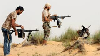 Fighters from a militia in Libya load their weapons