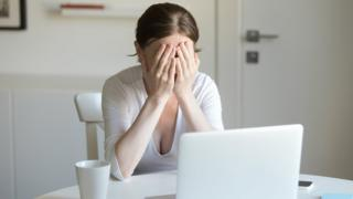 Woman working at desk with laptop, hands closing face