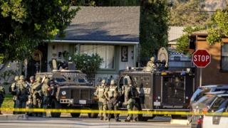 SWAT team moves in on a barricaded suspect on Fourth Street east of Orange Avenue after several people were shot at that location in Azusa, Calif.
