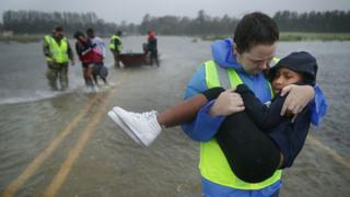 an emergency worker carries a child
