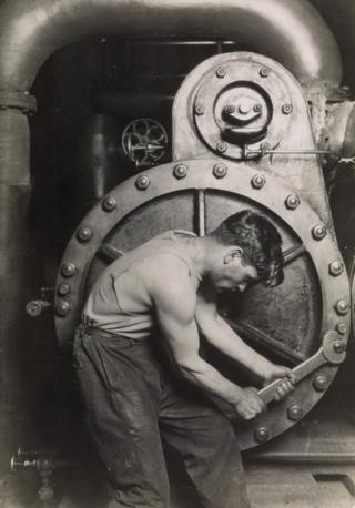 A mechanic uses a spanner on a steam pump.