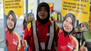 A Shell petrol station employee holds up life-sized cutouts depicting a female staff member, pictured in uniform with a black Muslim headscarf and placed beside individual self-serve petrol pumps as part of a promotional campaign, as they were pulled from display at a Shell station in Bentong, some 70 kms north of Kuala Lumpur in nearby Pahang state on July 4, 2017
