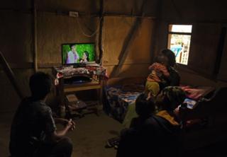 ઘરમાં ટીવી જોતાં લોકો