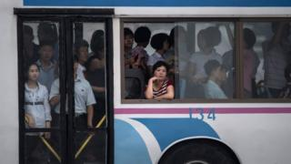 A commuter looks out from the window of a trolley bus tram in Pyongyang on 21 July