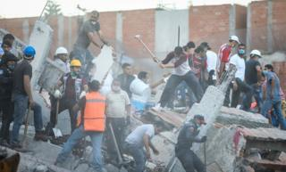 Rescuers with helmets and pickaxes clear rubble from damaged buildings