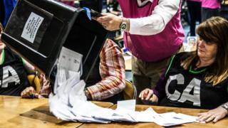 Vote counters sitting at a table as ballot papers are tipped out