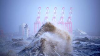 A huge wave with cranes and a light house in the background