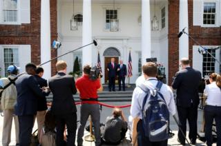 A velvet rope separates reporters from the man with the nuclear codes