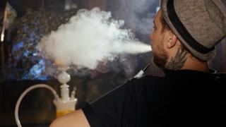 Hombre joven de espaldas fumando de una cachimba.