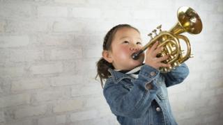 Una niña tocando la trompeta