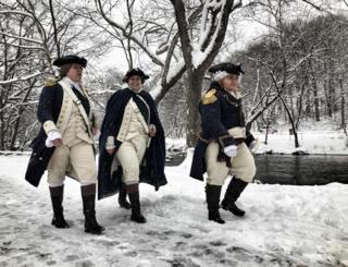 Three women wear American Revolution outfits while walking in snow