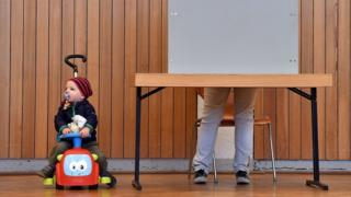 A child looks on as a voters fills out the ballot papers during the state elections in Hesse (Hessen) at a polling station in Ginsheim-Gustavsburg, central Germany