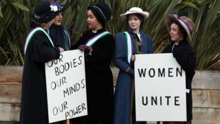 Students marking the anniversary by recreating a suffragette protest march