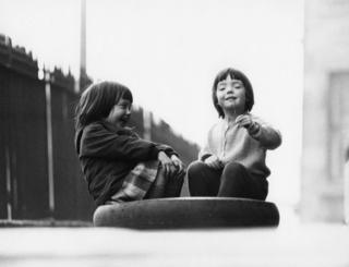 Two young girls playing in a tyre, 1966.