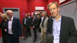 David Cornock reporting, watched by Jeremy Corbyn