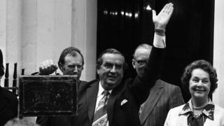 Chancellor of the Exchequer Denis Healey, holding the budget box and accompanied by his wife Edna, waves the crowd as they leave Number 11 (Eleven) Downing Street for the House of Commons where Mr Healey will present his budget