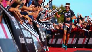 Jesse Thomas of the United States celebrates as he crosses the line to win Ironman Wales 2015