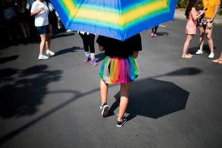 A woman marches in a rainbow-coloured skirt and parasol.