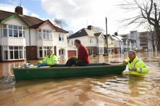 A resident is rescued from a home in a boat by the emergency services amid flooding in Hereford.