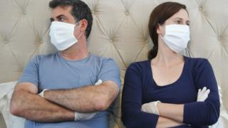 Couple wearing PPE and not talking