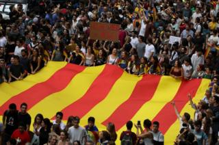 People carry a huge flag and placards during a demonstration two days after the banned independence referendum in Barcelona, Spain, 3 October 2017.