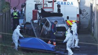 Gardaí at the scene of the burnt-out vehicle in Dublin