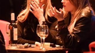 Women drinking outside a bar