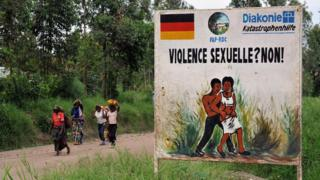 Congolese women walk past a sign opposing sexual violence on December 4, 2008 in Nyamilima, in Nord-Kivu, in the east of the Democratic Republic of Congo (DRC).