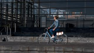 Woman riding bike past Senedd