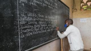 A pupil wearing a face mask as a preventive measure against the spread of the COVID-19 coronavirus writes on the blackboard in Yaoundé, Cameroon, 1st June 2020.
