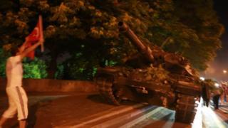 Tankı Türk bayrağıyla protesto eden bir kişi